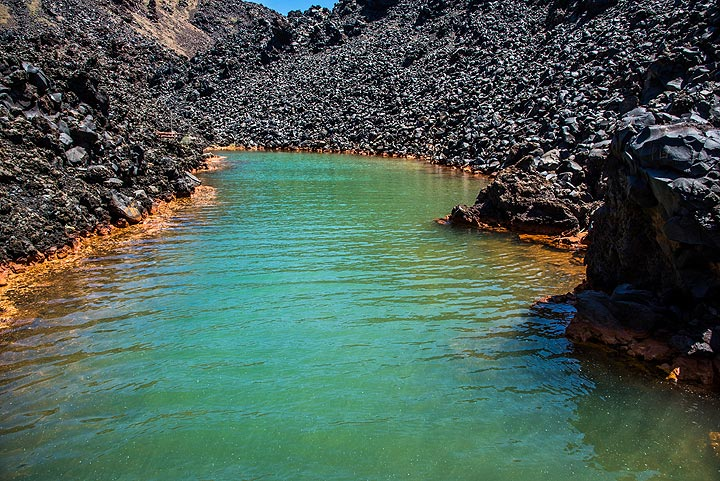 Nea Kameni's secret hot spring bay. Underwater springs deposit iron in the water, green at the bottom and oxidized to orange at the waterline. (Photo: Tom Pfeiffer)