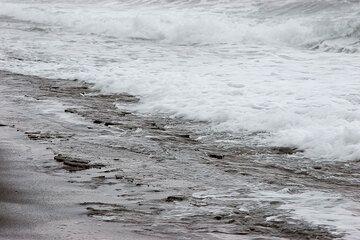 Spray of waves on the beach, exposing its beach rock (Photo: Tom Pfeiffer)