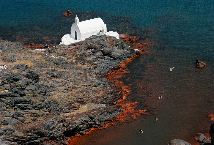 Agios Nikolaos chapel on Palea Kameni island, one of the two historic volcanic islands in the center of the Santorini caldera (Greece). The sea around the island with its small bays is a popular destination for boat cruises - swimmers enjoy the warm waters of the red iron bay. The orange stain of the rocks on the shore is the result of iron oxide deposit from an active hydrothermal vent system at the shallow sea floor around the Kameni islands. It releases heated, iron-rich waters and deposits a layer of iron-mud on the sea floor. (Photo: Tom Pfeiffer)
