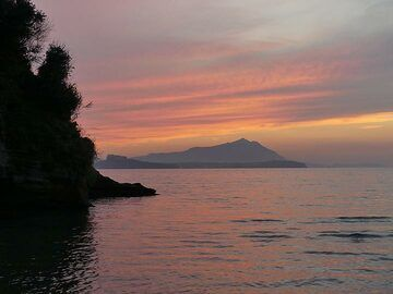 Pink and orange sky above the Phlegraean islands of Procida (central flat silhouette with building to the left) and Ischia (silhouette in the background with small mountain to the right). (Photo: Ingrid Smet)