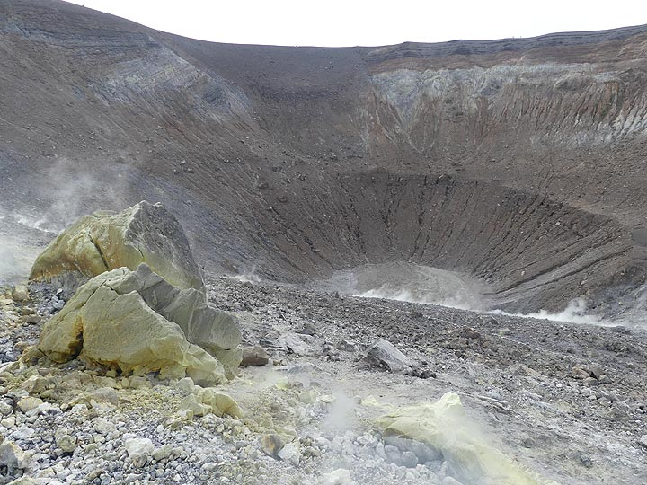 A large volcanic bomb coated by sulfur mineralisations lies on the rim of the impressive La Fossa crater of Vulcano. (Photo: Ingrid Smet)