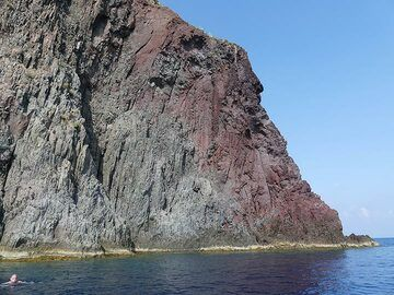 The outer zone of the volcanic neck of Strombolicchio is red-oxidised whilst the inner grey part clearly shows subvertical cooling joints. (Photo: Ingrid Smet)