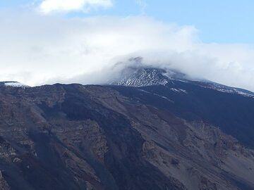 Before we return to our hotel the clouds that had previously covered Etna's summit area partially lift and uncover the snow covered goal of our next day's hike. (Photo: Ingrid Smet)