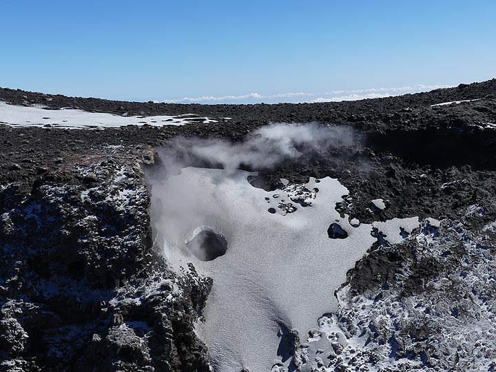 Continuous degassing and fumarolic activity arund the summit craters melts holes in the fresh snow blanket. (Photo: Ingrid Smet)