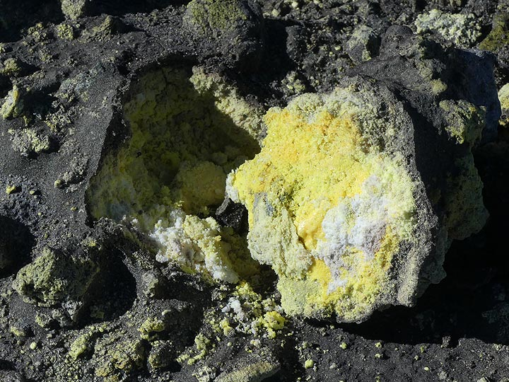 The E-NE rim of the Voragine - Bocca Nuova crater complex is the scene for intense fumarolic activity which has created a thick blanket of sulfur covered only by a thin later of ash. (Photo: Ingrid Smet)