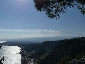 Looking southwest from the public gardens in Taormina towards Mt Etna which is about to be covered by afternoon clouds (summit with steam cloud center-right). (Photo: Ingrid Smet)