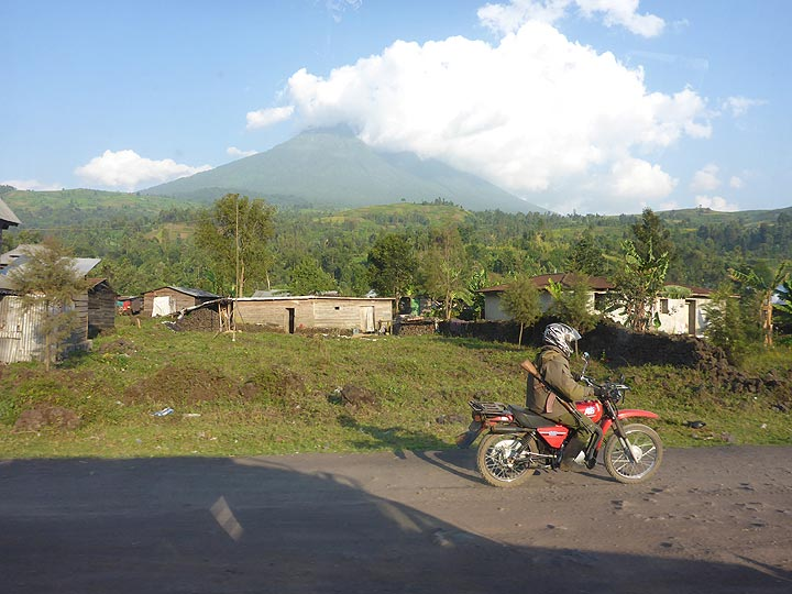Day 7 - Our motorcylce Virunga National Park escort accompanying us on the way back to Goma, with Mikeno volcano in the background (Photo: Ingrid Smet)