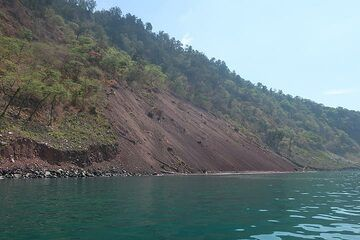 The inner coast of Rakata, where previous camps had been located. All of the approx. 30 m wide beach terrace was washed away during the tsunami, and parts of the cliff collapsed in a large landslide seen here in the foreground. (Photo: AndreyNikiforov)