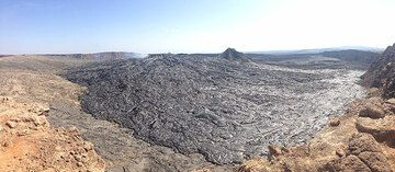 Panorama across Erta Ale´s caldera floor, clearly showing the large volume of fresh black shiny pahoehoe lavas that have recently overflowed from the lava lake which by now constructed its own containment rim (central-left in the background, where the gas plume rises from). (Photo: Hans and Jooske)