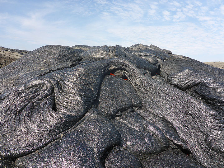 Intricate texture of the cooled silver to black crust of a fresh pahoehoe lava flow. Despite the seemingly solid crust, these flows are still very hot and liquid on the inside (given away by the red hot glow in folds between different branches). (Photo: Hans and Jooske)