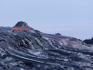 Exploding lava bubbles and pahoehoe lava overflow at the rim of Erta Ale´s perched lava lake. (Photo: Hans and Jooske)