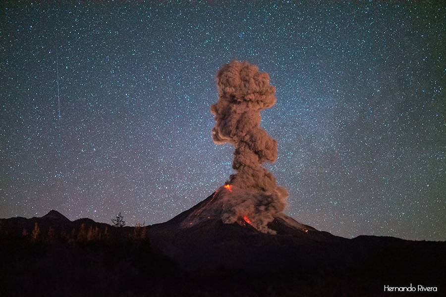 Colima volcano in Mexico during an intense eruptive phase: while several lava flows descend the southern and western flanks, fed by the summit lava dome, a pyroclastic flow caused by collapsing lava from one of the flows produces a dense ash cloud that rises approx. 2 km. A meteorite falls from the sky above the scene. (Photo: Hernando Rivera)