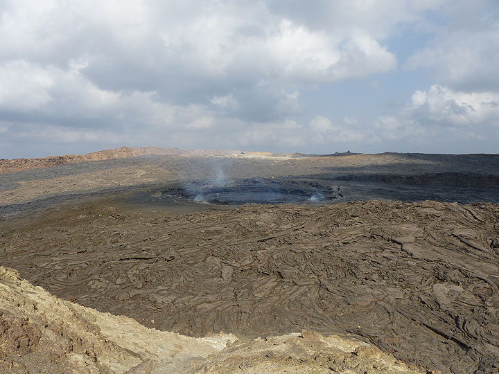 Image from 1 ago (November 2015) to compare the previous panorama with this overview onto the active lava lake and the wider caldera area around, where the darker brown coloured, narrow lava flows radiating outwards from the active vent onto the caldera flowrepresented the most recent lava overflows from 2010. (Photo: Ingrid Smet)
