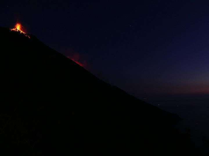 ...besides the glowing lava bombs on the upper parts of the Sciara one can also see a red glow about one third down, this is the light of active lava flows on the other edge of the Sciara reflected in their degassing plumes. (Photo: Ingrid)