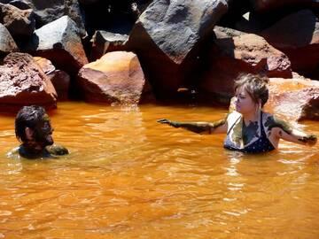 Tourists having fun in the ferrous volcanic spa of Nea Kameni island, Santorini archipelago, Greece (Photo: Janka)