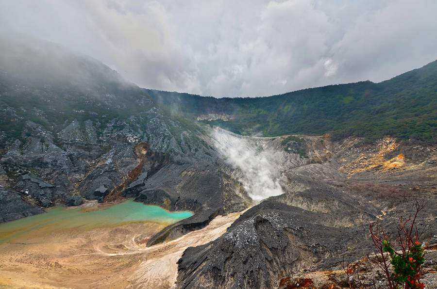 """Kawah Ratu - Mt. Tangkuban Perahu, West Java, Indonesia  Mt. Tangkuban Perahu is Bandung's most famous volcano just 28 km north of the city. This volcano has a distinctive shape, like an upside down boat (Tangkuban Perahu means, in fact, """"up-turned boat""""), it  has three craters into which areas tourists can walk through. These three craters are: Kawah Ratu, Kawah Domas and Kawah Upas. Kawah Ratu, which means """"Queen's Crater"""", is today just a big gray hole, which sometimes has a pool of water at its center. Poisonous gases sometimes accumulate in Kawah Ratu, thus making it somewhat of a risk to descend to the crater floor. Beyond the saddled shaped depression on the far side of Kawah Ratu is the still active Kawah Upas, the oldest crater on the mountain. On the very far western cliff we see a spot where all vegetation has been destroyed by constantly rising sulfurous vapors. On the crater walls, note the various layers of material consisting of rock, sand, and pebbles. Overtime, new craters have formed again and again in a rather consistent shift from west to east. (Photo: JessyEykendorp)"""