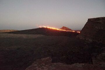 16 Jan evening: View from NW towards the south crater with its lava lake from campsite. What used to be a pit crater has been replaced by a sizeable lava shield currently feeding an overflow to the western caldera wall. (Photo: Paul Reichert)