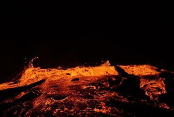 Zoom onto the lava overspilling the perched lava lake at the top of the shield on the whole western side (night 17-18 Jan). (Photo: Paul Reichert)