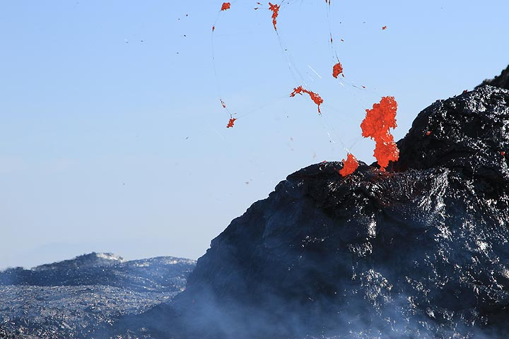 Formation of Pele's hair - thin glassy filaments of lava as molten spatter is ejected and torn into threads by exploding gas bubbles from the lava lake. (Photo: Paul Reichert)