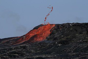 """A string of lava is thrown into the air as a larger gas bubble explodes while lava is surging out from the bowl.  """"We were observing 20-30 m fountains splashing on the norther side of the wall."""" (Enku) (Photo: Paul Reichert)"""