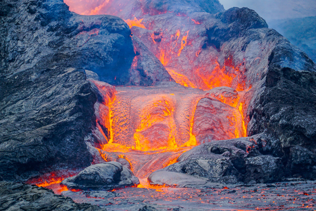 At the end of a fountaining / overflow episode of the vent, the surfaces are glowing red, while the lava flows downhill. (Photo: Ronny Quireyns)