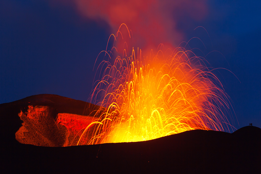 Active cone of Plosky Tolbachik volcano in strombolian activity. Note the silhouettes of people for scale to the lower right. (May-2013) (Photo: Sergey Krasnoshchokov)