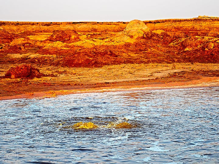 Yellow acid water bubbling up from a large hydrothermal pond near Dallol and Assale salt lake (c)