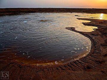 Sun set over a large acid hydrothermal pond and salt deposits near Dallol and Assale salt lake (c)