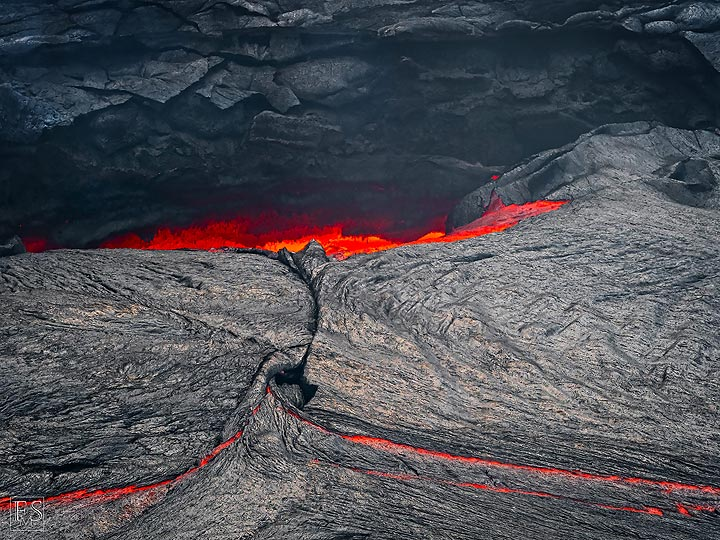 View into the cavity at the edge of the lake where the liquid lava flows into (Erta Ale fissure eruption) (c)