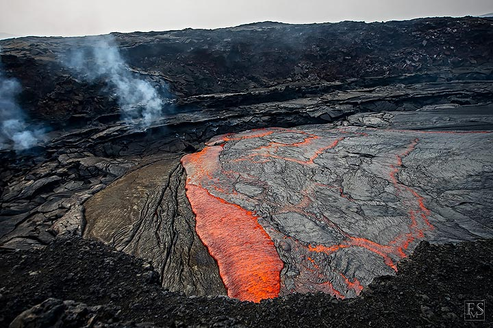 Recently cooled black crust is overrun and consumed by red hot liquid lava that itself quickly cools and crusts over (Erta Ale fissure eruption site) (c)