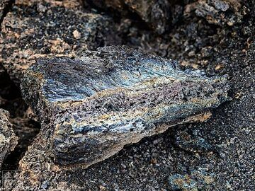 Close up of fresh piece of lava with iridescent colours and gas bubbles (c)