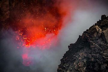 Large explosions of gas bubbles in the active lava lake throw up spatter of red hot lava high above the lake's surface that is partially covered by volcanic gasses (Erta Ale south crater in the summit caldera) (c)