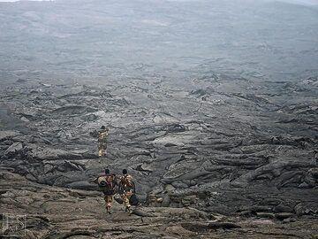 Ethiopian military and Afar policement escort walking across the vast lava flows in the summit caldera of Erta Ale (c)