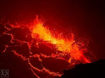 Gas rising up and exploding through the lava lake's surface creates lots of spattering at the edge of the lake (south crater inside Erta Ale's summit caldera) (c)