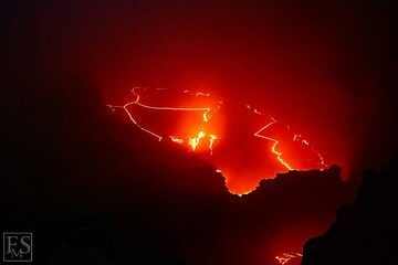 Nighttime view of the cracked zigzag pattern of the thin crust on top of the active lava lake inside the south crater of Erta Ale's summit caldera (c)