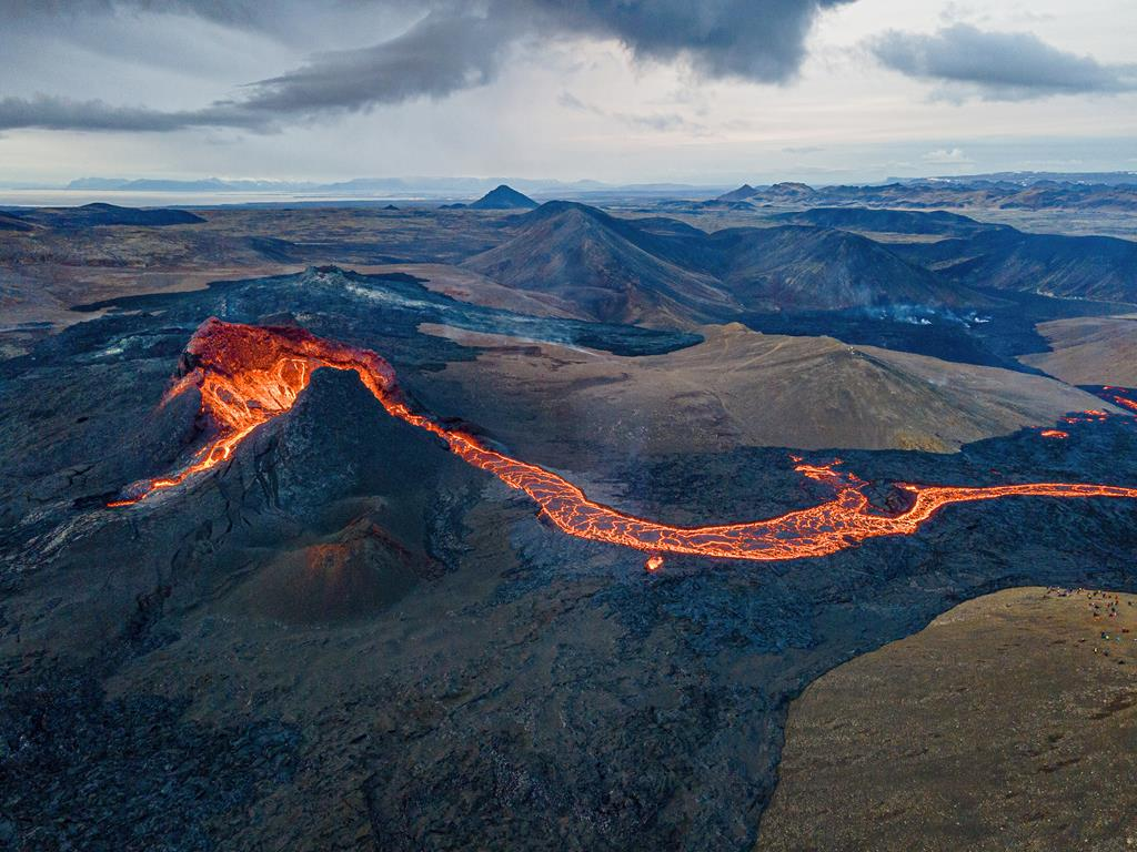 Aerial view towards the SW over the active cone and the lava flow. Reykjanes southern coastline is visible in the background. (Photo: World-Geographic)