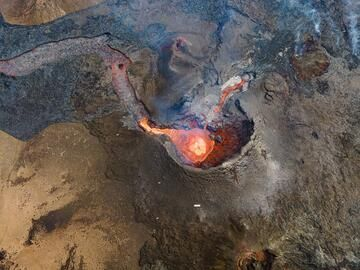 Vertical aerial shot into the main cone during a quiet phase; a small pond of lava fills the vent. (Photo: World-Geographic)