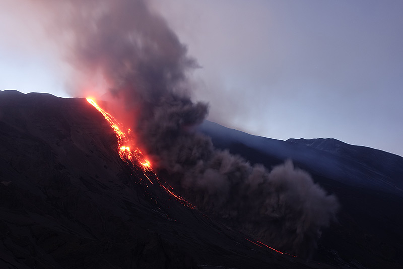 Lava flow at dusk with an ash plume from a small pyroclastic flow. (Photo: roland)