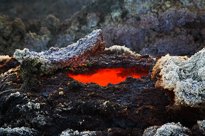Roof of a lava tube with whitish sulfate minerals formed by escaping gasses reacting with the lava rock. (Photo: Emanuela / VolcanoDiscovery Italia)