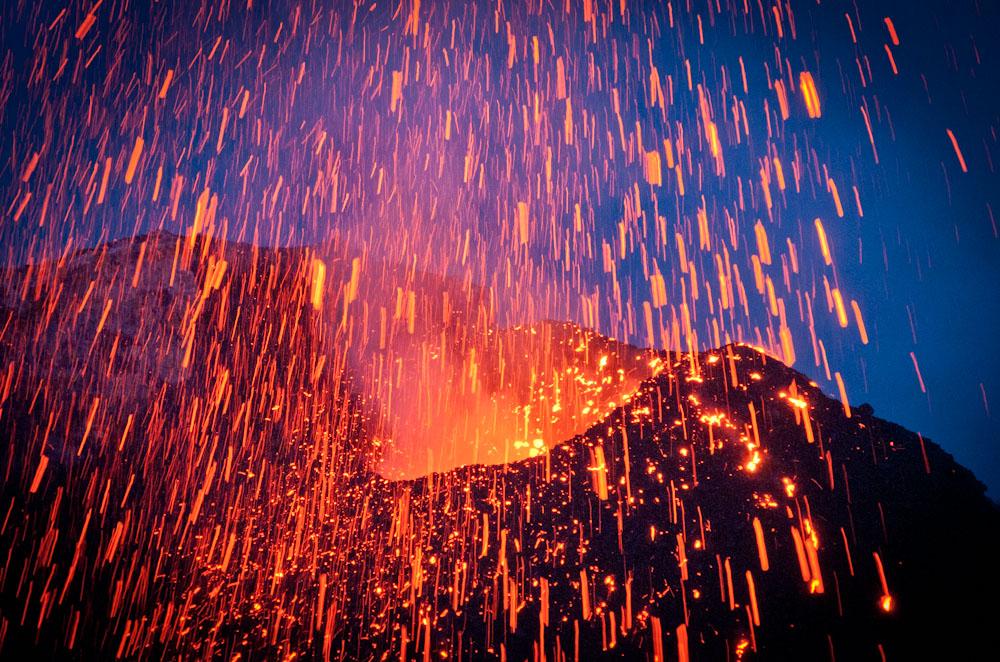 """Feu d'artifice au Stromboli, un volcan actif en Italie.  La photo a été prise au printemps 2009 et montre une explosion du cratère nord-est du Stromboli dans le crépuscule du soir. Pendant la première moitié de 2009 en particulier, ce cratère était en activité très spectaculaire et avait rapidement construit un nouveau cône qui dominait la terrasse du cratère du Stromboli. Depuis ailleurs, bien d'autres changements se sont produites, mais ce cône est toujours l'une des principales caractéristiques du cratère aujourd'hui. Nous avons choisi cette photo comme la """"photo du mois"""" déc 2011 et nous félicitons Christian avec un bon de voyage de 500 euros! (Photo: muepla)"""
