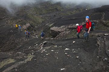 To get to the rim of Marum, we first have to circle it and descend a bit again, following a ridge in a moon-like landscape of ash, erosion gullies and (fortunately not recent) volcanic blocks and bombs.  (Photo: Tom Pfeiffer)