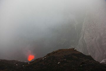 Manchmal lichten sich Nebel und die vulkanischen Dampfschwadem im Krater genug, um die beeindruckenden, senkrechten inneren Kraterwände zu erkennen. (Photo: Tom Pfeiffer)