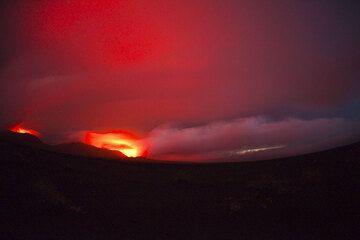 Weitwinkelaufnahme über der Kaldera mit von Blitzen erhellten Gewitterwolken über den rot glühenden Kratern. (Photo: Tom Pfeiffer)