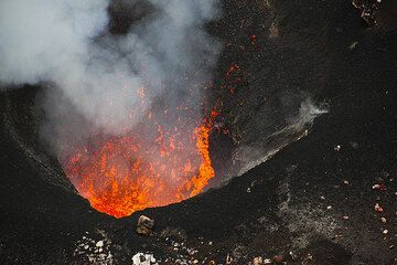 Sometimes, spattering is stronger when larger lava bubbles burst on the surface of a little lava lake inside the vent.  (Photo: Tom Pfeiffer)