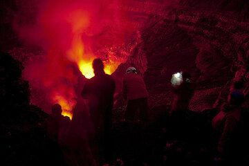 The group observing the lava lakes at night, when the crater is only illuminated by the red lava glow. (Photo: Tom Pfeiffer)