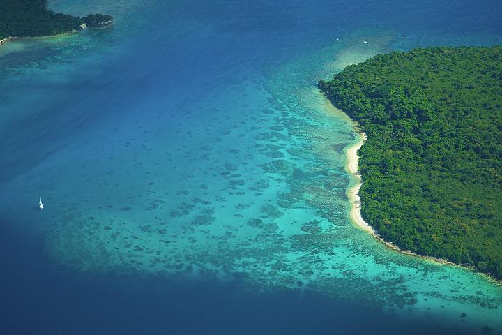 Sailing boat between tropical islands (Photo: Tom Pfeiffer)