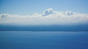 """Approaching Ambrym Island, we can see the thick volcanic gas plume (""""vog"""") howering above the caldera. (Photo: Tom Pfeiffer)"""