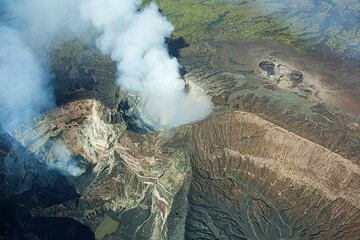 The complex Marum crater with its active lava pond (left) and the main crater Mbwelesu (right) as well as the Niri Mbwelesu pit crater near the rim of Marum (center), probably containing a crusted-over and active lava pond as well seen from the air. The smaller collapse pit Niri Mbwelesu Taten in the background S of Marum (Photo: Tom Pfeiffer)