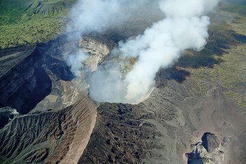 The complex of Marum crater and its surrounding pit craters: Mbwelesu (l), Marum's west pit with the lava lake (a.l.), smoking Niri Mbwelesu (c), and Niri Mbwelesu Tatem pit crater (l.r.). (Photo: Tom Pfeiffer)