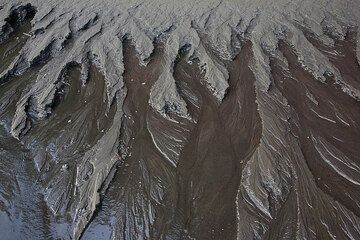 Warm spring water seeps out from the volcanic sand near sea level and creates a bizarre miniature landscape of canyons and stream valleys.  (Photo: Tom Pfeiffer)